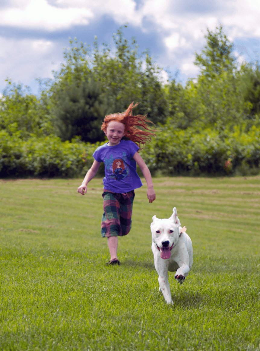 Image of a girl running after a dog at Dog Mountain, Home of Stephen Huneck Gallery