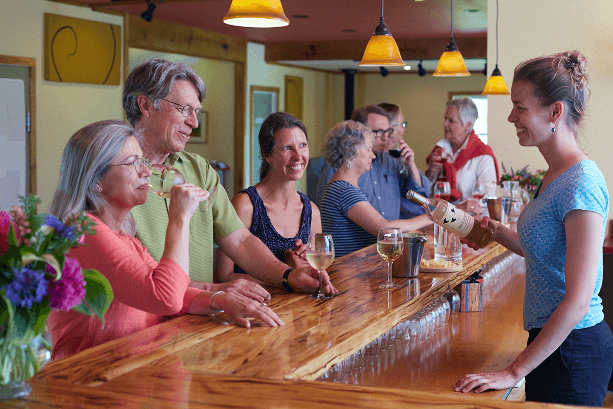 Image of people at the tasting room bar enjoying wine