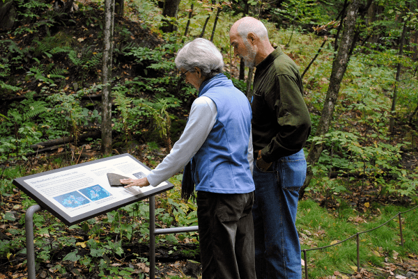 Image of couple reading a sign in the Montshire Museum of Science woodland garden.