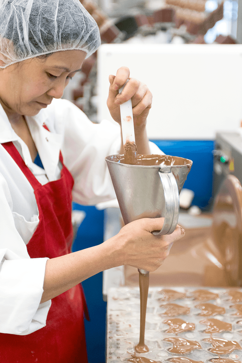 Image of a woman pouring chocolate into a mold