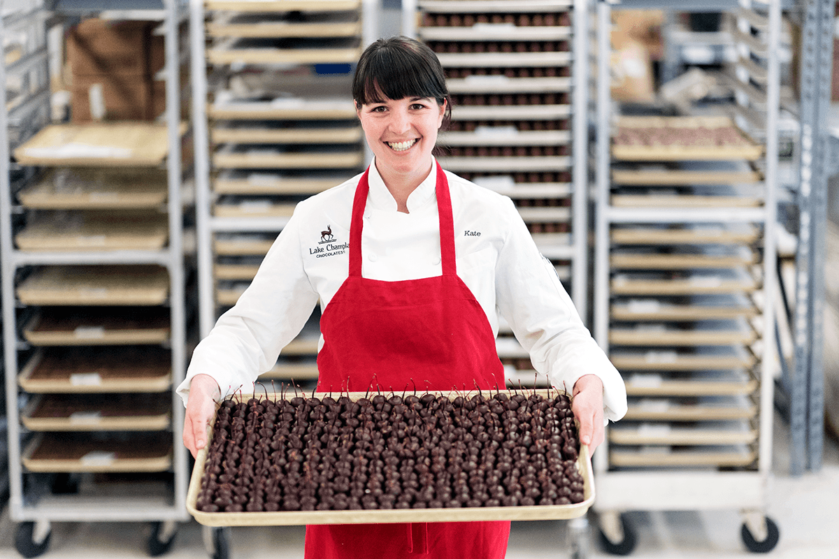 Image of woman holding a tray of Lake Champlain Chocolates