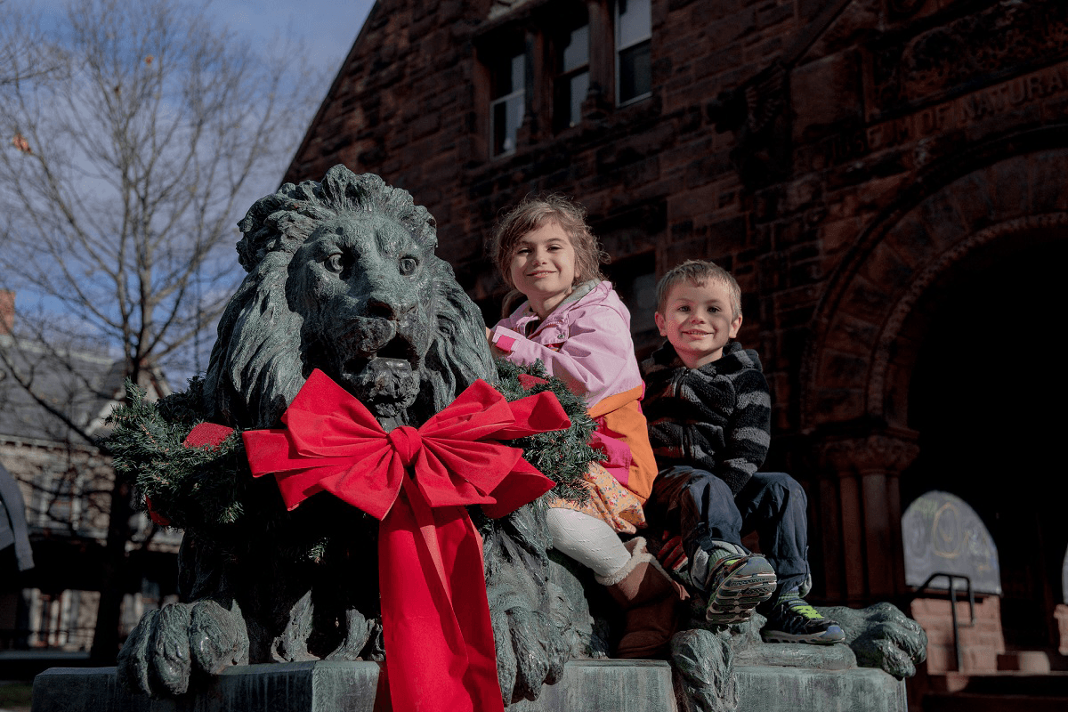 Image of kids on the lion wearing a bow at Fairbanks Museum