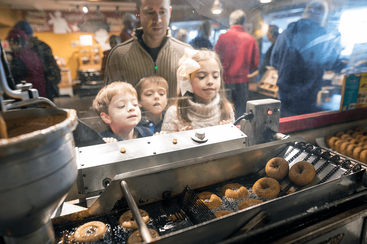Image of family watching donuts come out of the fryer