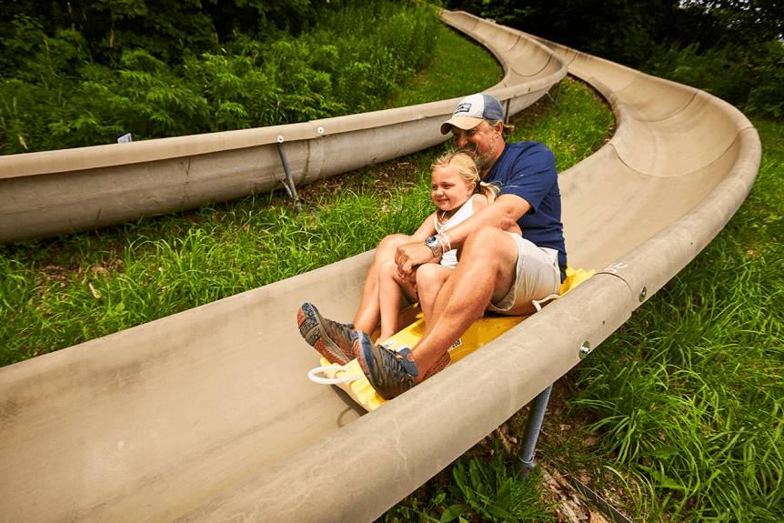 Image of father and daughter on alpine slide