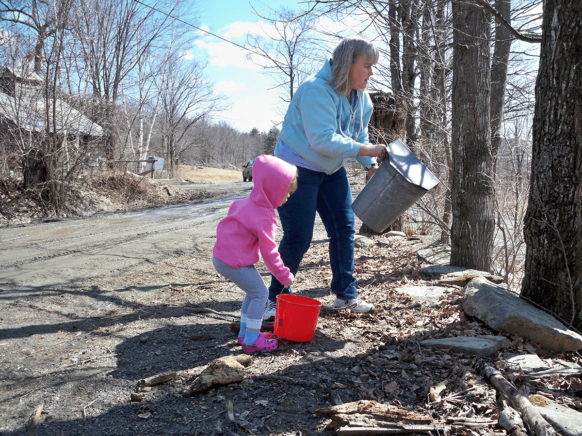 Image of woman and little girl gathering sap at Sugarbush Maple and Cheese Farm