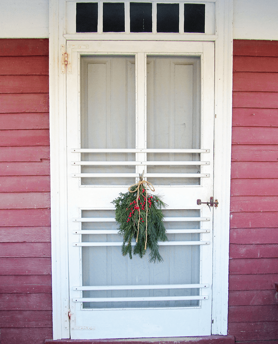Image of boughs of holly on a door at Shelburne Museum