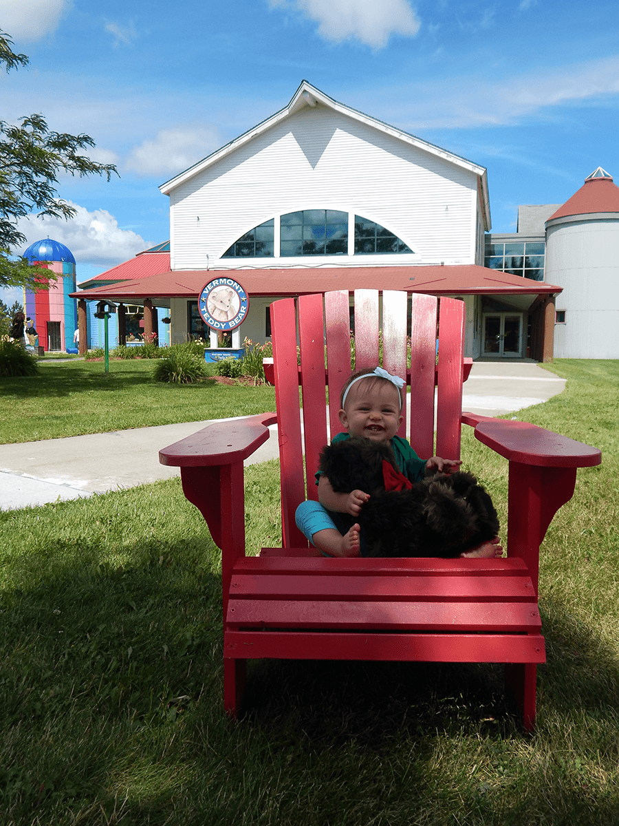 Image of a baby sitting in an Adirondack chair at Vermont Teddy Bear Company