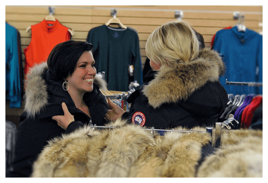 Image of women trying on coats at Farm-Way