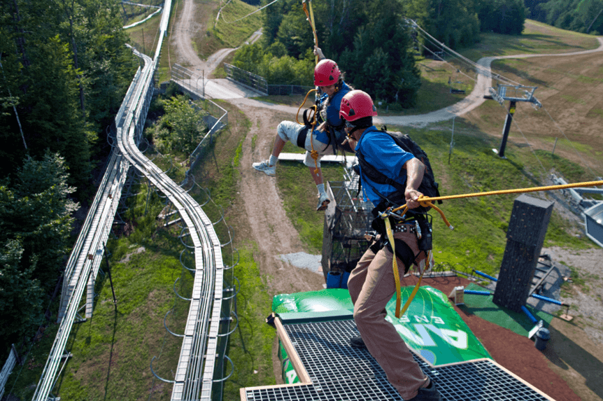 Image of two people getting ready to launch on the zipline at Okemo Mountain Resort