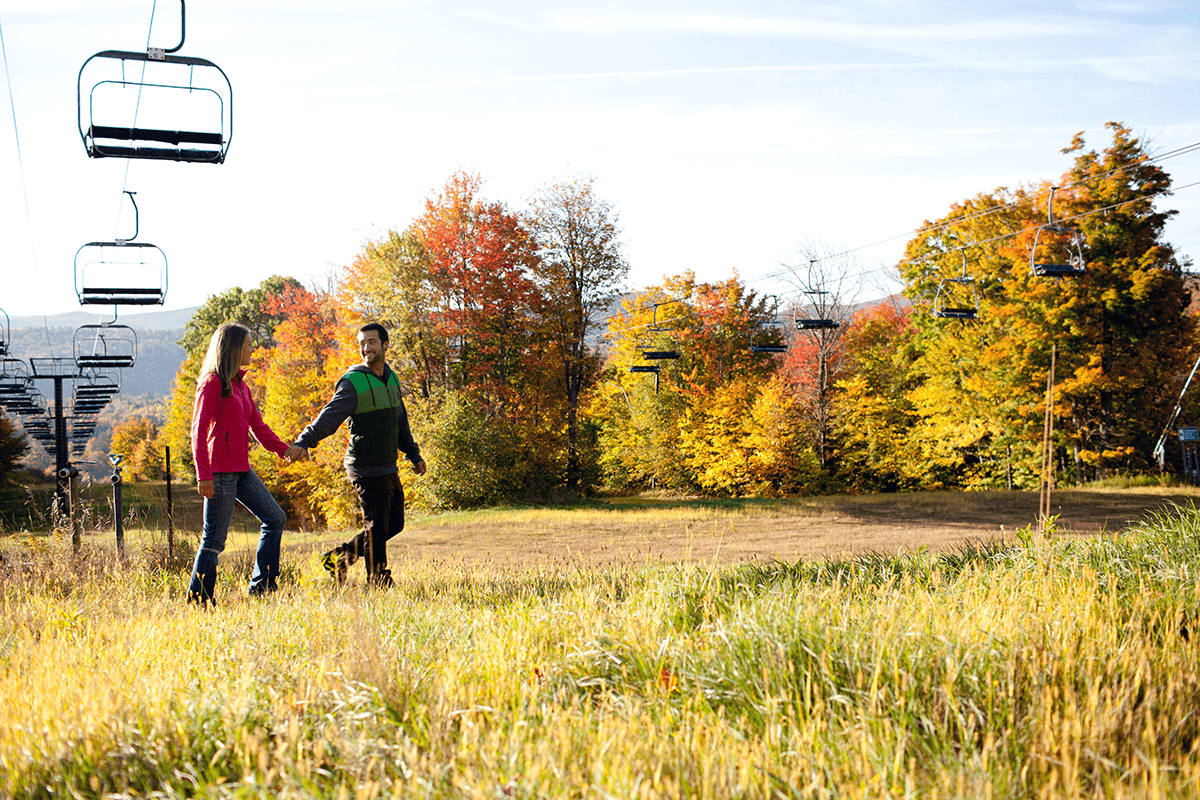 Image of a couple walking in the fall on a trail at Okemo Mountain Resort