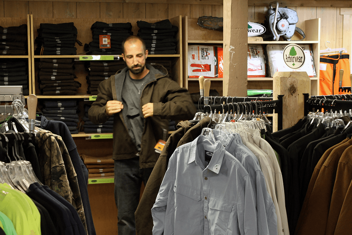 Image of man trying on a coat at Farm-Way