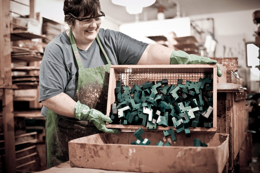 Image of woman dumping wood blockes into a bin at Maple Landmark Woodcraft