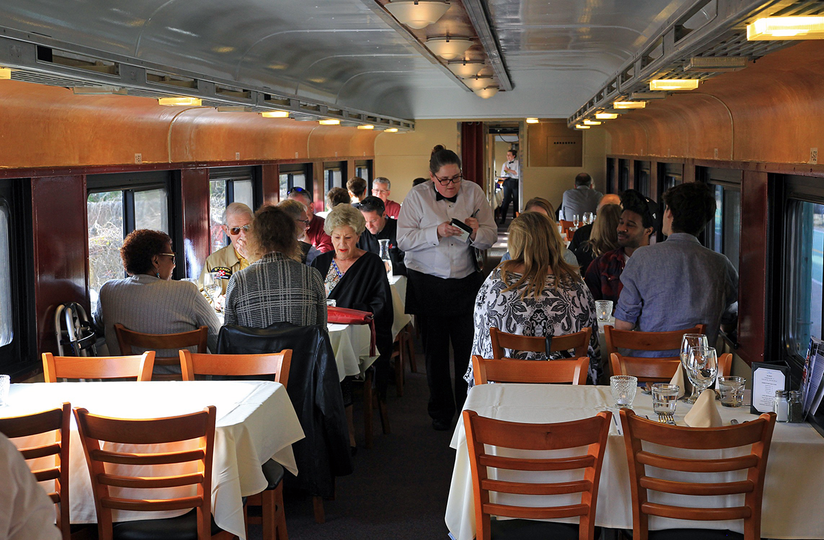 Image of waitress taking orders in the dining car aboard the Green Mountain Railroad