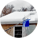 Snow is piled on a roof and the snow is removed by a pole and shovel