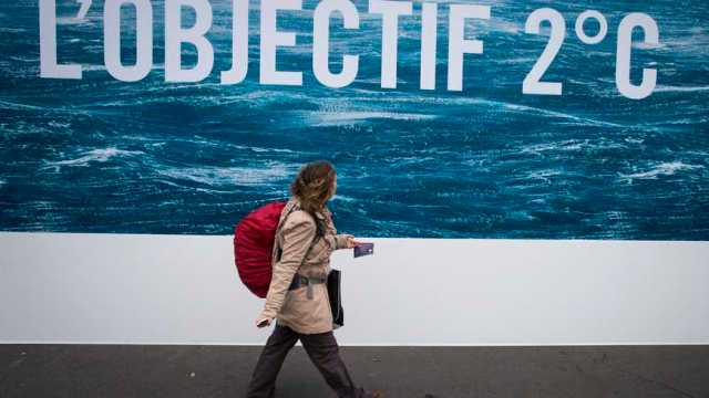 epa05022001 A woman walks in front of a poster bearing the message 'Objective 2 degrees' in reference to the projected agreement to limit the increase of global warming to two degrees Celsius, in Paris, France, 12 November 2015. France will host the COP21 Climate Change Conference from 30 November to 11 December 2015.  EPA/IAN LANGSDON (MaxPPP TagID: epalive902558.jpg) [Photo via MaxPPP]