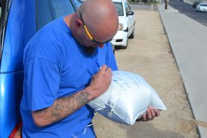Frank Adams writing a message to his daughter Sofia Adams. (Photo by Diana Cabral, Victor Valley News)