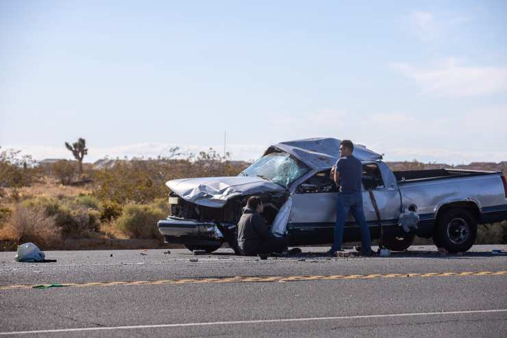 A good samaritan stand with the woman trapped inside the truck as they wait for help to arrive. (Hugo C. Valdez, Victor Valley News)