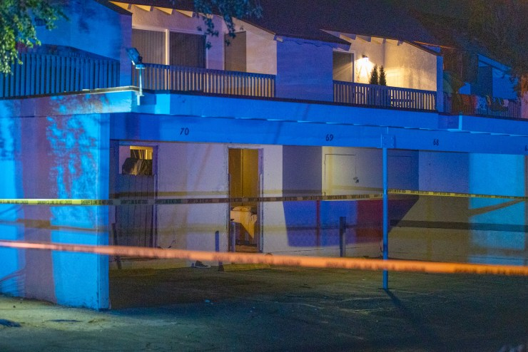 Crime scene tape near an open door in the rear of an apartment. (Gabriel D. Espinoza, Victor Valley News)