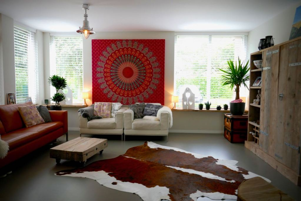 Modern interieur met een koeienvel op de grond en warme kleuren gebruikt