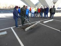 National Park Service staff Aaron LaRocca and WABA staff Jeff Wetzel demonstrate how to remove a concrete parking stop.