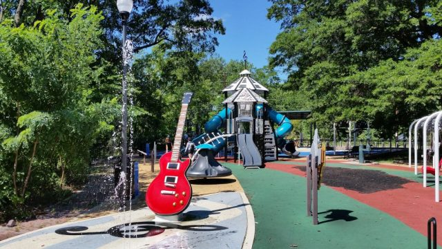 A playground on a sunny day. there is a giant guitar in front and the slides structure behind has keyboard printed roof. There is a water splash park.