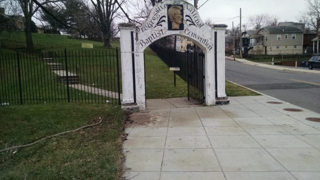 """Front white gate of a fence with peeling white paint. THere is an gold image of Lincoln on top of the arch and it reads """"Progressive National Baptist Convention"""" in black cursive font."""