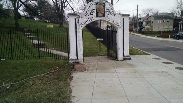 "Front white gate of a fence with peeling white paint. THere is an gold image of Lincoln on top of the arch and it reads ""Progressive National Baptist Convention"" in black cursive font."