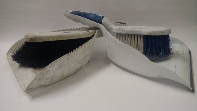 Glamor shot of two white dustpans and handbrooms on a white background. Both dustpans are used and dirty though the dustpan on the left is clearly more used.