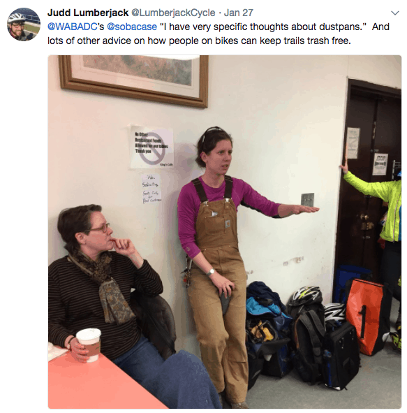 "Screen caption of a tweet reading ""@WABA's @sobacase ""I have very specific thoughts about dustpans."" And lots of other advice on how people on bikes can keep trails trash free."" There is a photo of a woman in brown workpants overalls talking and leaning up against a wall. Another woman on the left is thinking, a pile of bike gear is on the right with the arm of a person is high visibility jacket on the far right of the frame."