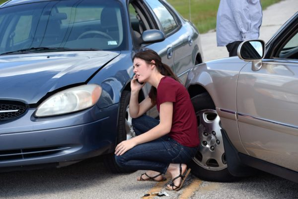 Young woman making phone call after accident. Wade Insurance Agency