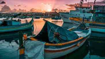 Widok łodzi zacumowanej przy brzegu Malty o zachodzie słońca