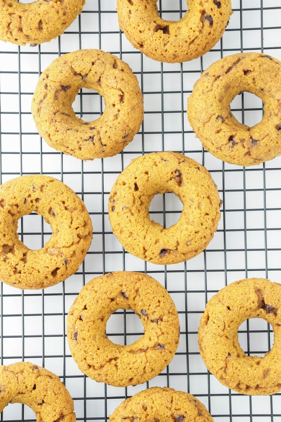 Healthy Pumpkin Chocolate Chip Baked Donuts! with caramel glaze! #coconutoil #wholewheat #bakeddonuts #recipe | www.wakeuptowaffles.com