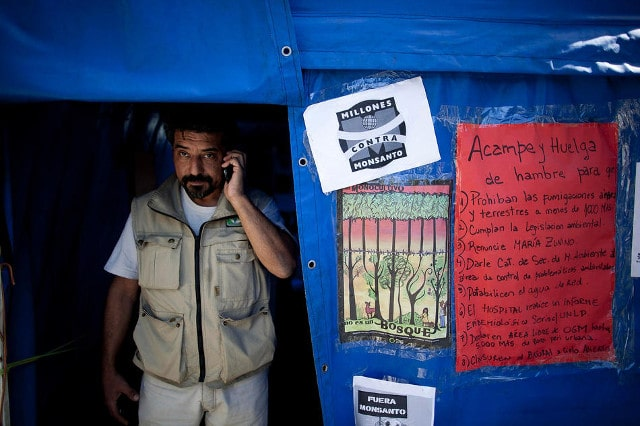 Activist Oscar Alfredo Di Vincensi has been fighting that agrochemical spraying not be allowed within 1,000 meters of homes. Pictured here in the main square of Alberti, in Buenos Aires province, Argentina, April 16, 2013. Di Vincensi stood in a field waving a court order barring spraying within 1,000 meters of homes in his town of Alberti; a tractor driver doused him in pesticide. CREDIT: Natacha Pisarenko/AP
