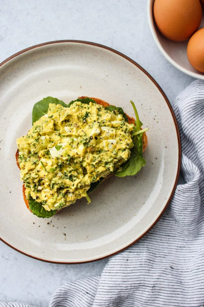 white plate with mashed avocado egg salad sandwich over a slice of toast