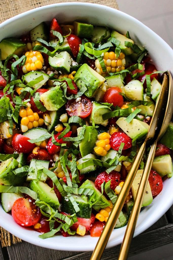 closeup shot of white bowl with corn, tomato, avocado, strawberry, basil, feta salad and gold serving spoons