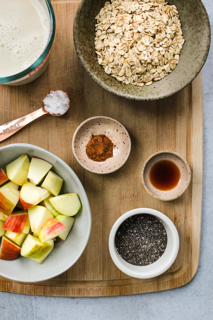 wood cutting board with bowls of oatmeal ingredients