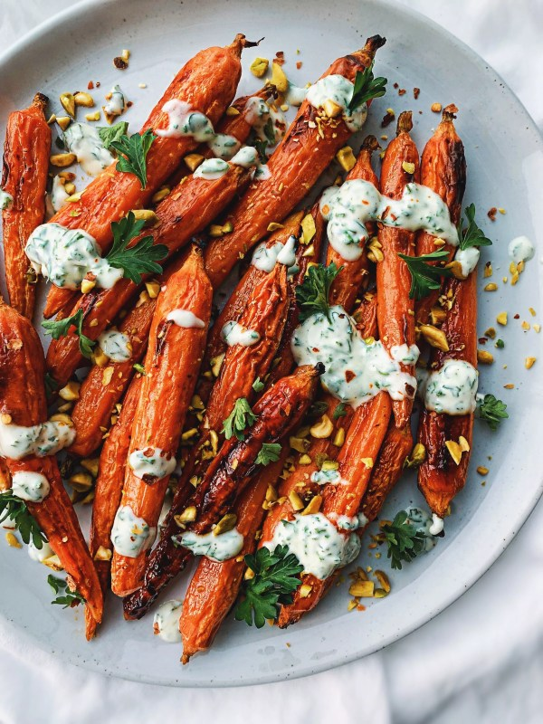 Plate of roasted carrots drizzled with yogurt sauce, chopped pecans, and parsley