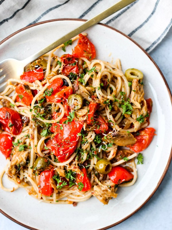 spaghetti with canned mackerel, red peppers, tomatoes, olives, and parsley on white plate with gold fork