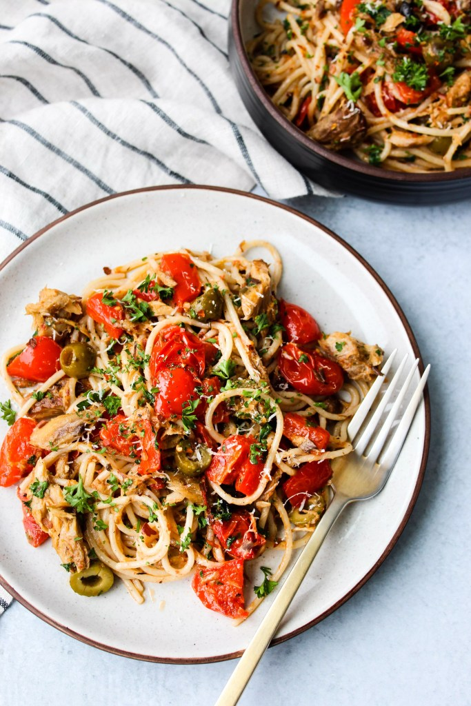 two plates of spaghetti with canned mackerel, red peppers, tomatoes, olives, and parsley
