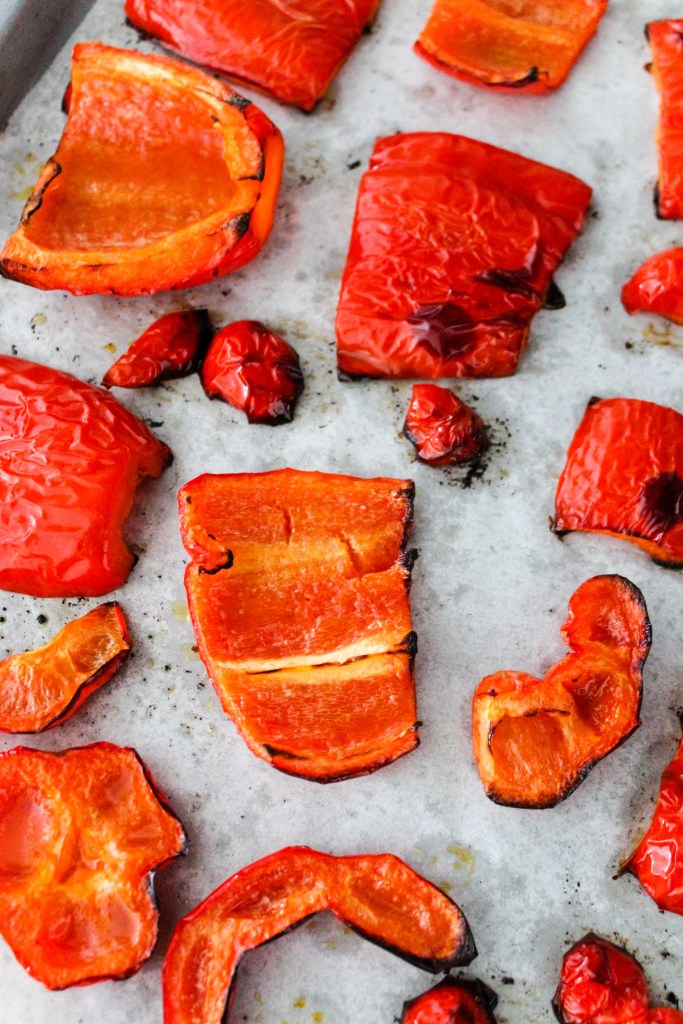 roasted red bell peppers on a baking sheet