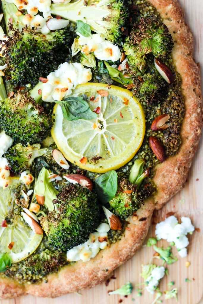homemade pizza with roasted broccoli, pesto, lemons, goat cheese crumbles, and almonds on cutting board