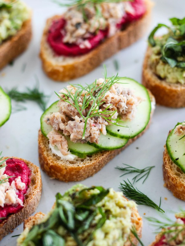 blue plate topped with canned salmon crostini, cream cheese, and dill