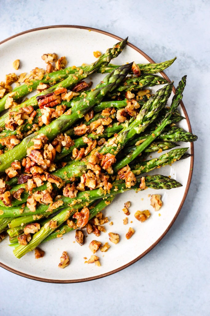 Roasted asparagus with chopped pecan parmesan on a white plate