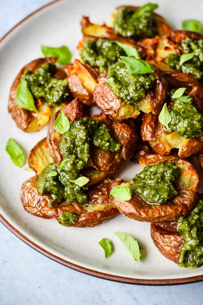 smashed red potatoes topped with pesto and basil leaves on white plate