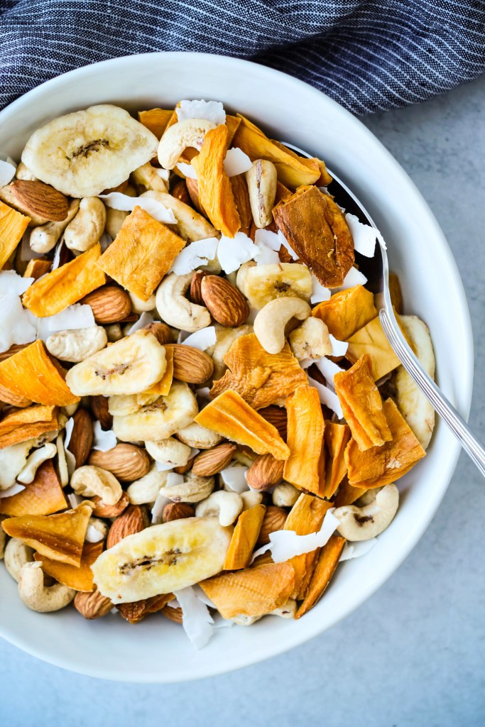 tropical trail mix with dried mangos, banana chips, coconut chips, almonds, and cashews in a white bowl
