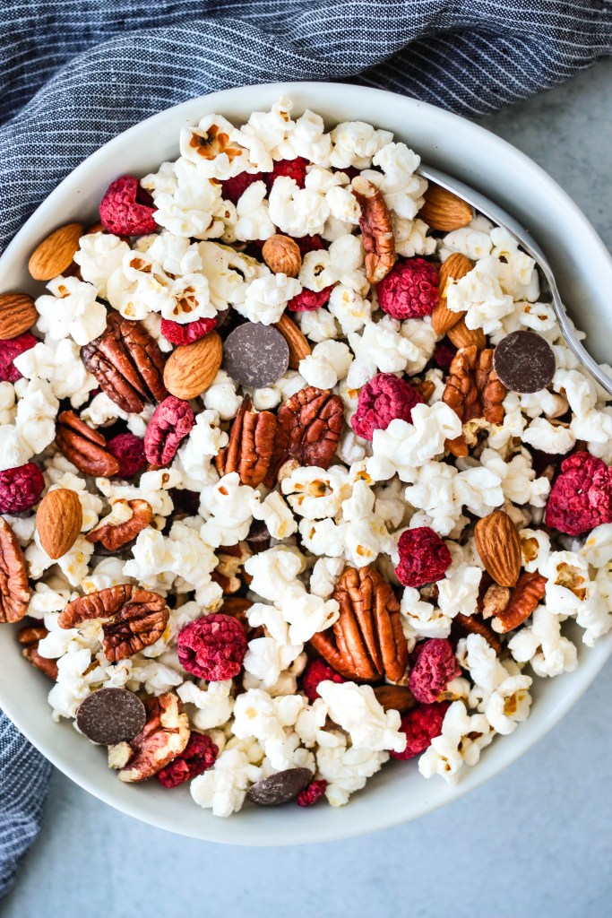 homemade trail mix with popcorn, chocolate chips, pecans, and almonds in a white bowl