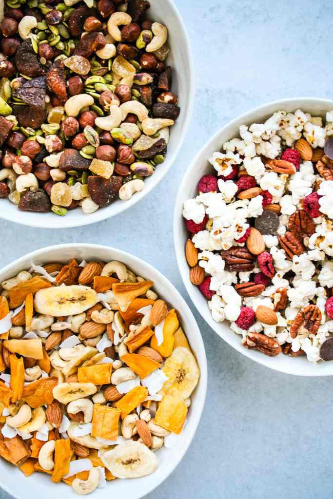 three white bowls of different homemade trail mix combinations