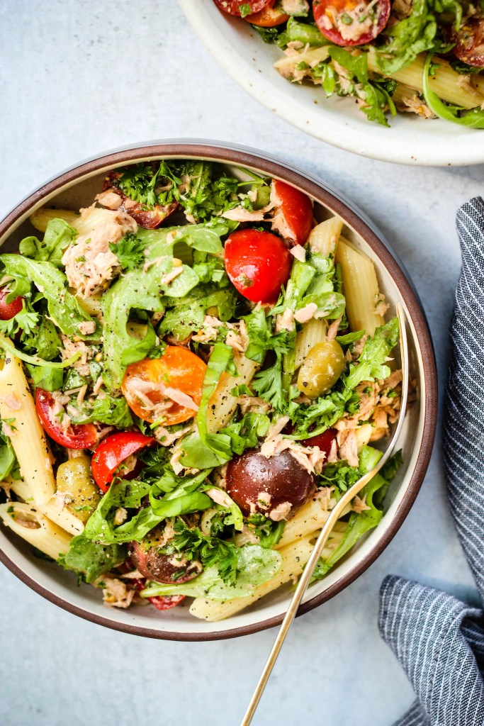 healthy tuna pasta salad with olives, tomatoes, arugula, and herbs