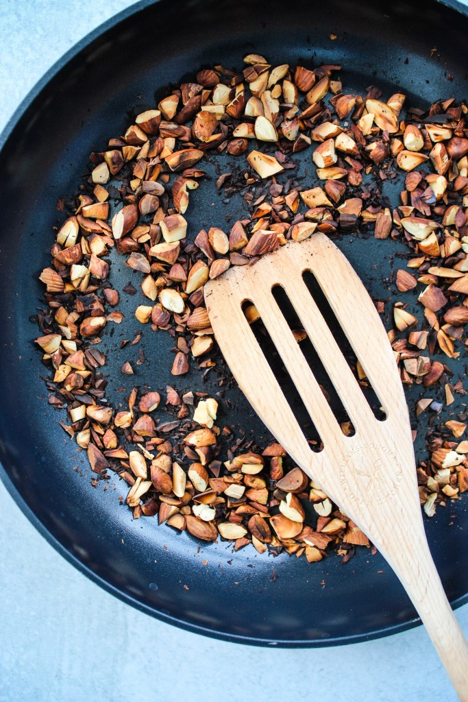 chopped almonds toasting on a frying pan