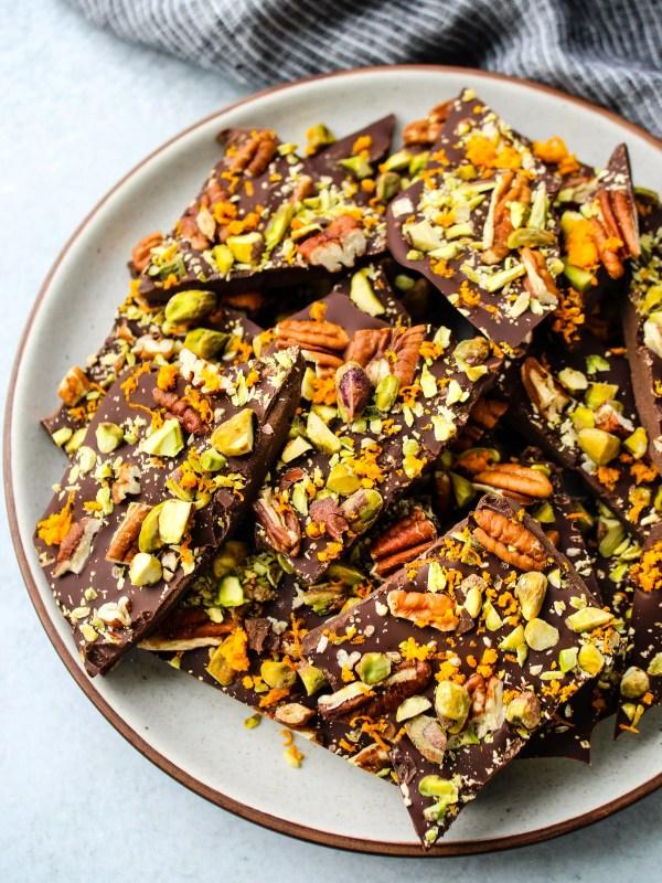 pieces of dark chocolate bark with orange zest, pistachio, pecans
